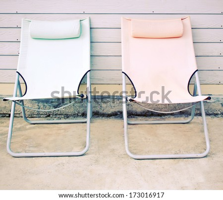 Two beach bench in front of the house with retro filter effect - stock photo