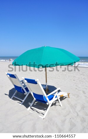 Two beach chairs and umbrellas on the beach - stock photo
