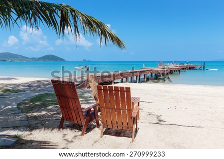 Two beach chairs on idyllic tropical sand beach. - stock photo
