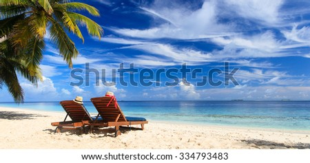 Two beach chairs on the tropical sand beach, panorama ideal for banners - stock photo