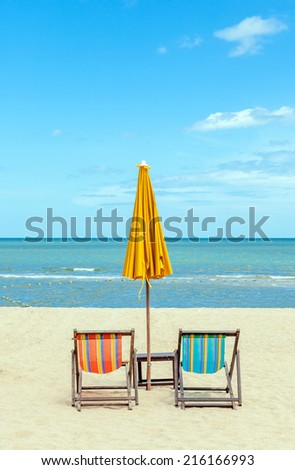 Two beach chairs with sun umbrella on beautiful beach. Concept for rest, relaxation, holiday, spa, resort. - stock photo