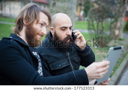 two bearded modern man working on tablet at the park - stock photo