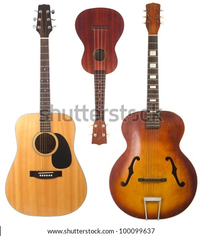Two beautiful acoustic guitars, one antique one modern, and a ukulele isolated on white background - stock photo