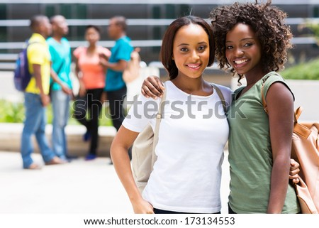 two beautiful african american college friends on campus - stock photo