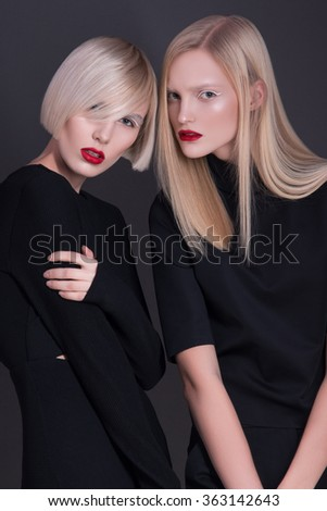 Two beautiful amazing fashion model posing and looking in camera. Sexy blonde, blonde hair woman. Studio shoot, shooting. Bright make up, hair style, red lips. Strong angry girls, dark grey background - stock photo