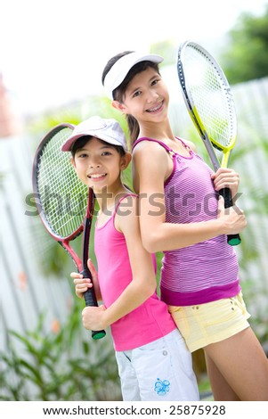 Two beautiful and fit sisters back to back with tennis racket each - stock photo