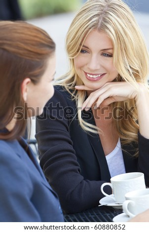 Two beautiful and sophisticated young women friends having coffee around a modern outdoor city cafe table - stock photo