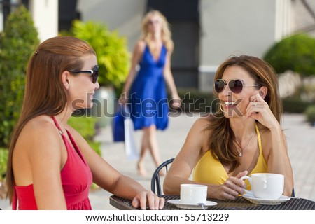 Two beautiful and sophisticated young women friends wearing sunglasses and having coffee around a modern city cafe table With their friend arriving with shopping bags in the background - stock photo