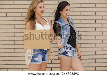 Two beautiful and young girlfriends having fun, in front of a brick wall - stock photo