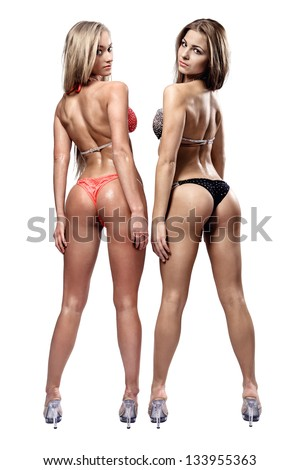 Two beautiful athletic girl wearing bikini posing over white background - stock photo
