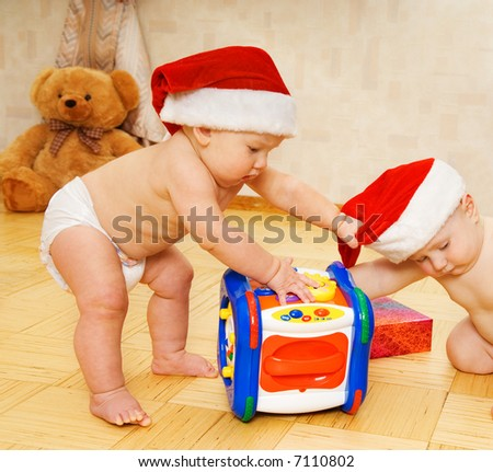 Two beautiful babies in Christmas hats - stock photo