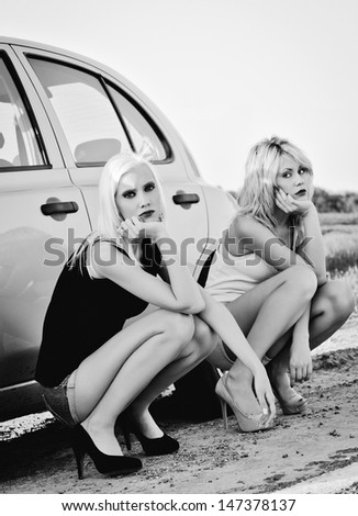 Two beautiful blonde girls sitting near their broken car and waiting for help. Black and white - stock photo