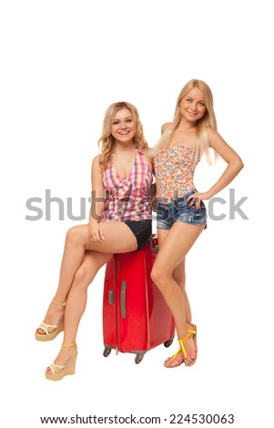two beautiful blonde girls wearing jeans shorts with  big red suitcase isolated on white  - stock photo