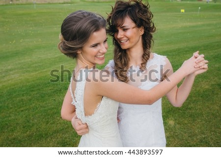 Two beautiful brides dancing  on the green field of the golf club - stock photo