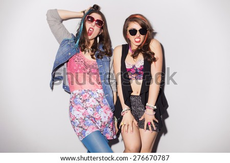 Two beautiful brunette women (girls) teenagers spend time together having fun, make funny faces. Retro outfit: bright blue tights, jeans jacket, shorts in sequins, and colored strand of hair - stock photo