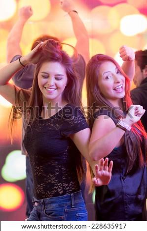 two beautiful brunette young fun girls dancing in a club - stock photo