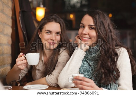 Two beautiful cheerful female friends in a cafe bar - stock photo