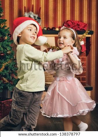 two beautiful child dancing near christmas tree - stock photo