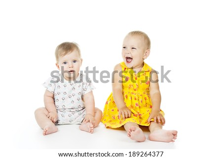 two beautiful child sit and play isolated on white background - stock photo