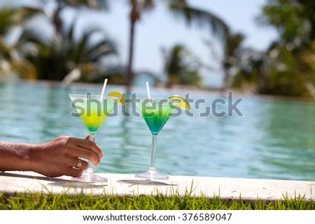 Two beautiful cocktail glasses on exotic resort near swimming pool. - stock photo