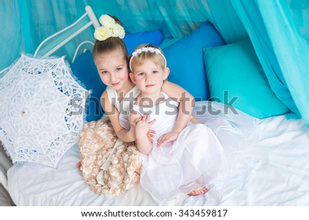Two beautiful elegant angel sisters in evening dresses and flowers in haur sitting on princess bed and whisper secrets ready for wedding and birthday - stock photo
