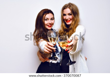Two beautiful elegant women celebrate hen-party and drinking champagne . Best friends wearing black and white stylish evening outfits .Bright make up, red lips. Indoors, b&w crazy party. Cheers. - stock photo