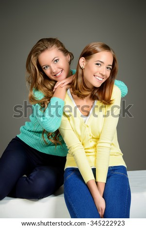 Two beautiful fashion models posing at studio in bright casual clothes. Beauty, fashion. - stock photo