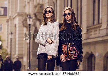 two beautiful fashion models posing outside wearing a grey sweater with leather shorts, studded ankle boots and a fringed cardigan, black T-shirt, embroidered A-line skirt  heeled ankle boots - stock photo