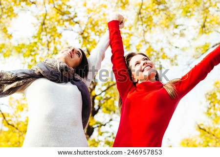 Two beautiful female enjoying in the park on autumn day - stock photo