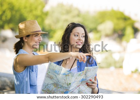Two beautiful female friends searching a place on the map - stock photo
