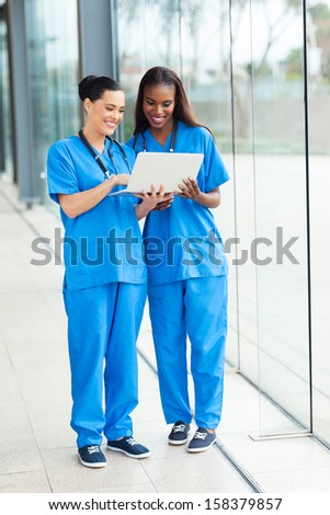 two beautiful female healthcare workers using laptop - stock photo
