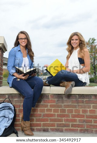 Two beautiful female students together on campus - sitting with books - stock photo