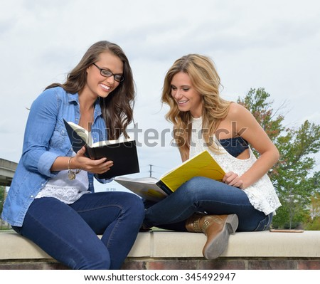 Two beautiful female students together on campus - sitting with books - pointing out passage in book - stock photo