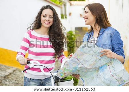 Two beautiful female tourists searching a place on the map - stock photo