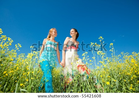 Two beautiful girl in white clothes go to the yellow flowers - stock photo