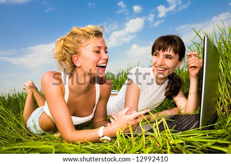 Two beautiful girl in white clothes on a laptop computer outdoors. Lay on the green grass. - stock photo