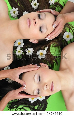 Two Beautiful girl with flower in spa  having massage - stock photo