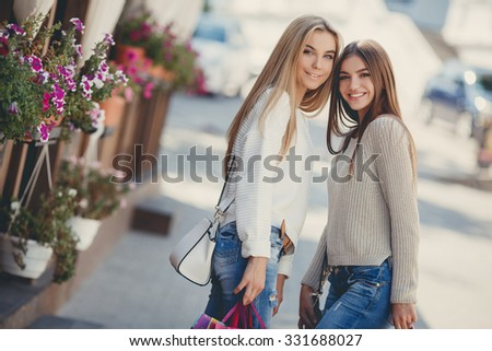 Two beautiful girlfriends with with Shopping Bags. Two women enjoy shopping. Portrait of two friends shopping together. shopping bags - stock photo