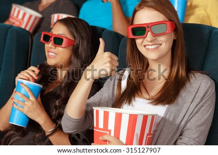Two beautiful girls at the cinema watching 3D movie - stock photo