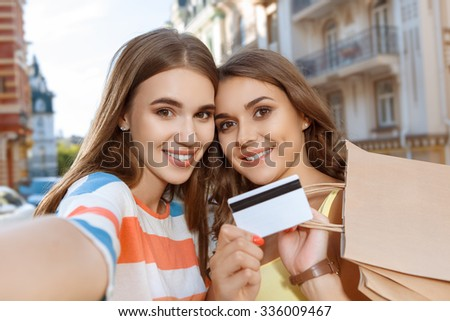 Two beautiful girls doing selfie with shopping bags and credit card - stock photo