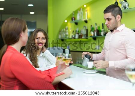 Two beautiful girls flirting with handsome barman - stock photo