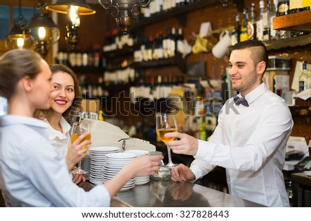 Two beautiful girls flirting with handsome barman in interior - stock photo