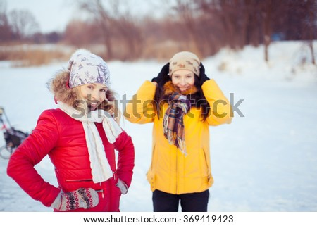 two beautiful girls ice skating outdoor on a warm winter day. - stock photo