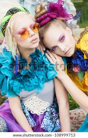 Two beautiful girls in a garden. Outdoors - stock photo