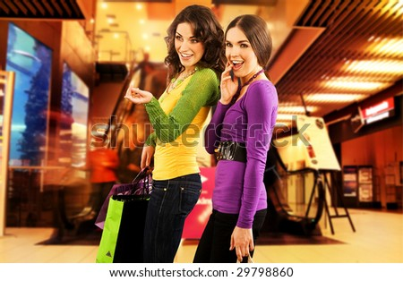 Two beautiful girls in a shopping center - stock photo