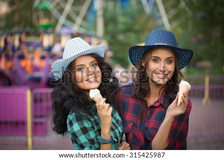 two beautiful girls in cowboy hats eating ice cream - stock photo