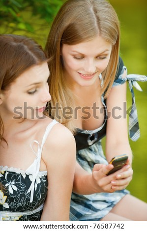 Two beautiful girls in summer city park and read sms on mobile phone. - stock photo