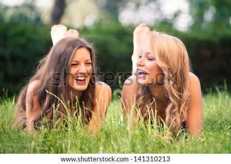 Two beautiful girls laughing together lying on grass outdoors in a park. - stock photo