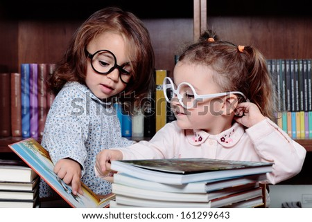two beautiful girls learning in the library - stock photo