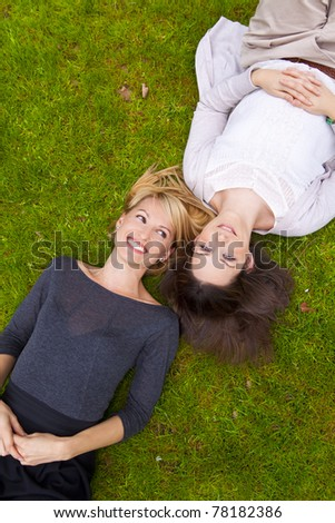 Two beautiful girls lying in the grass and laughing. - stock photo